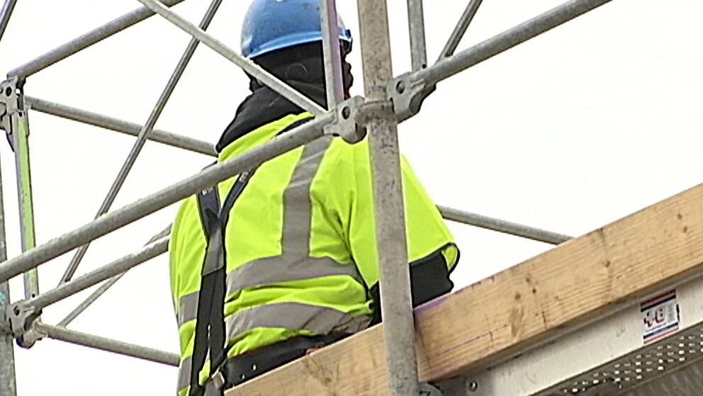 En byggnadsarbetare står på en byggarbetsplats.
