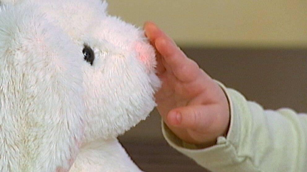 närbild på en babyhand som sträcker sig emot en leksak