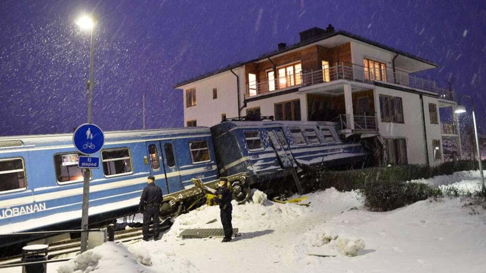 Tågvagnar som lutar och har kört in i hörnet på ett bostadshus. Det snöar.