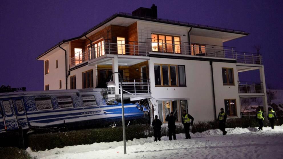 Tågvagnar som lutar och har kört in i hörnet på ett bostadshus. Det snöar och är mörkt. Polisern framför