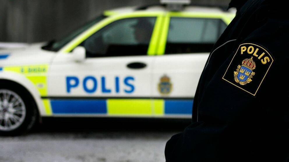 Polis med polisbil i bakgrunden.