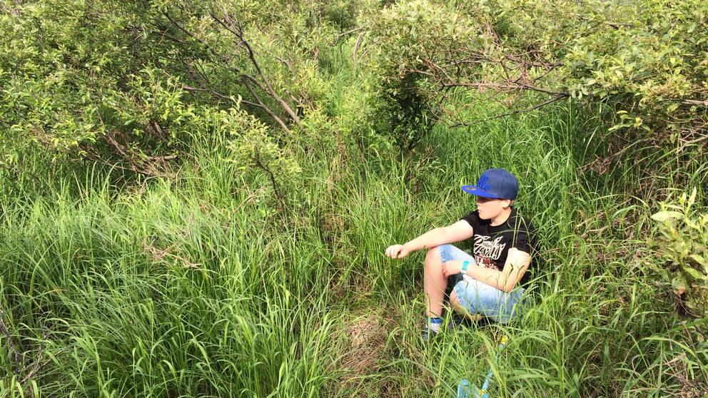 En kille sitter i gräs