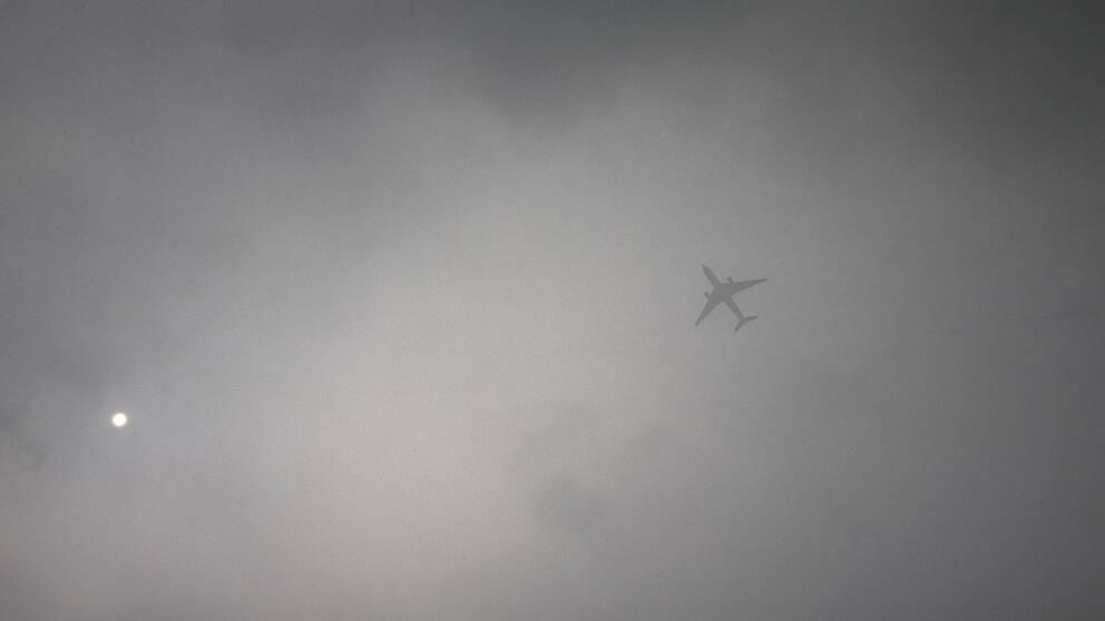 Ett passagerarplan flyger genom dimman i Peking.