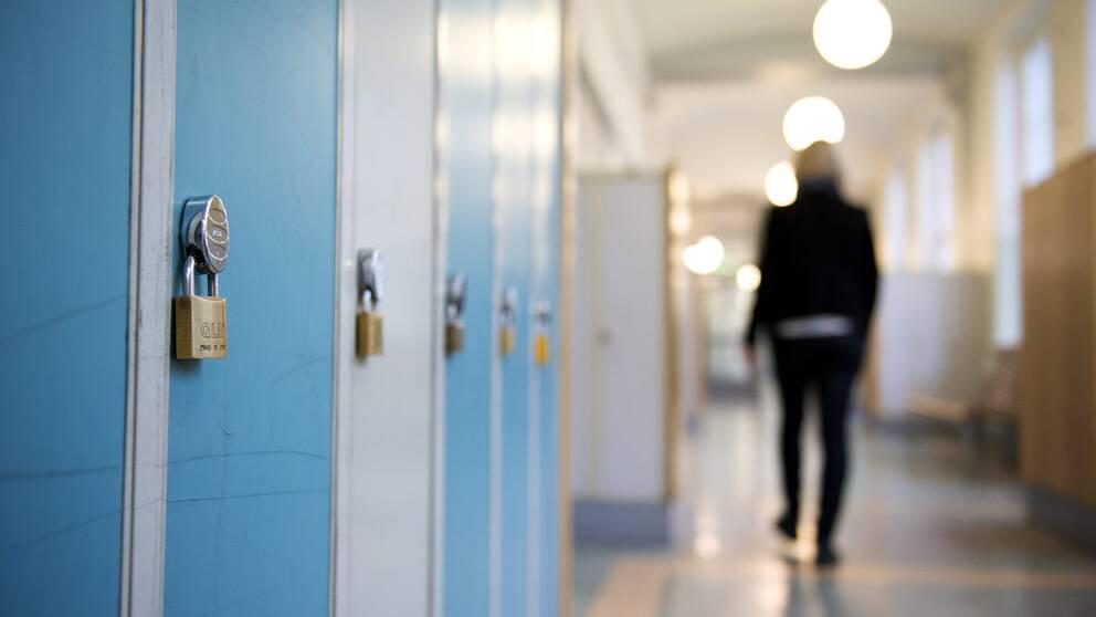 En elev går i skolkorridor.