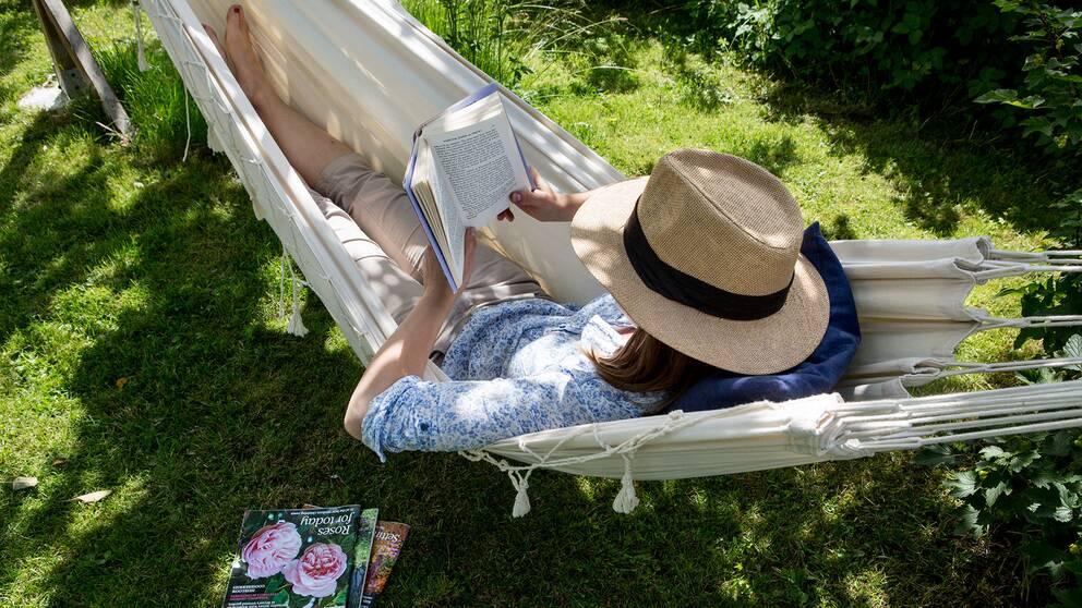 Kvinna läser i en hängmatta.
