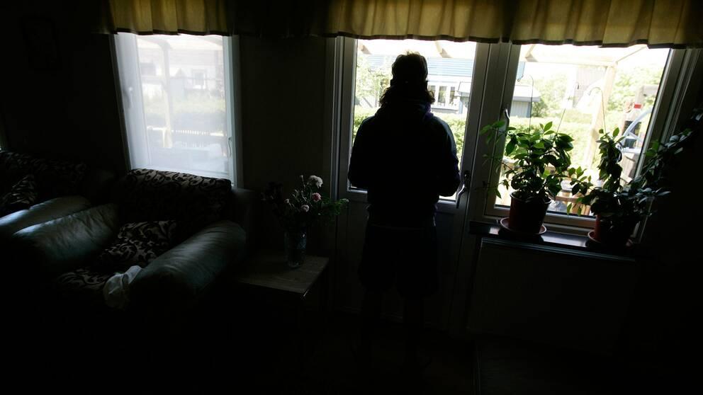 En man som tittar ut genom ett fönster