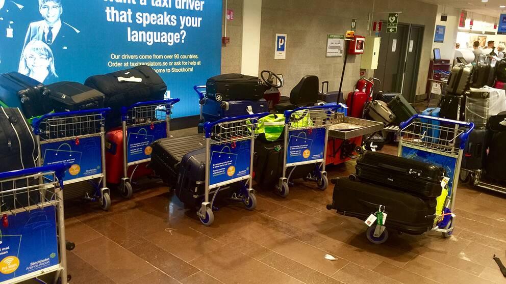 Bagagevagnar fyllda med bagage står vid en vägg.