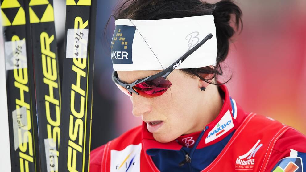 Marit Björgen med skidor och solglasögon.