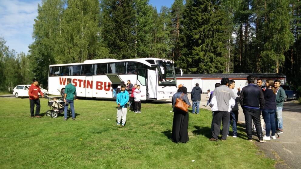 asylsökande i krokströmmen står utanför en buss