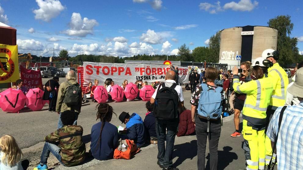 Demonstranter mot förbifarten sitter på marken