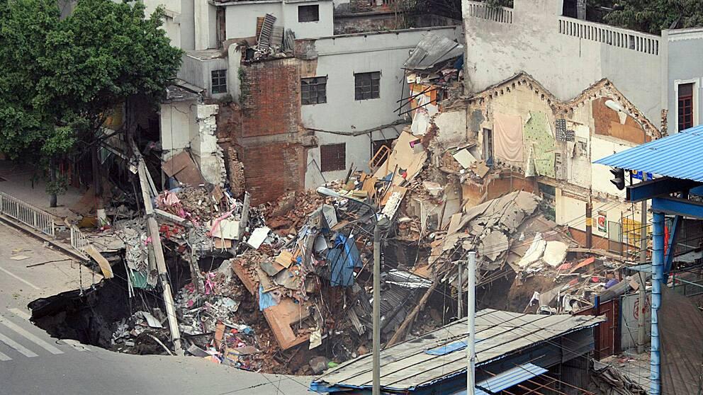 Flera hus kollapsade när ett hål öppnade sig mitt i gatan i den kinesiska staden Guangzhou.