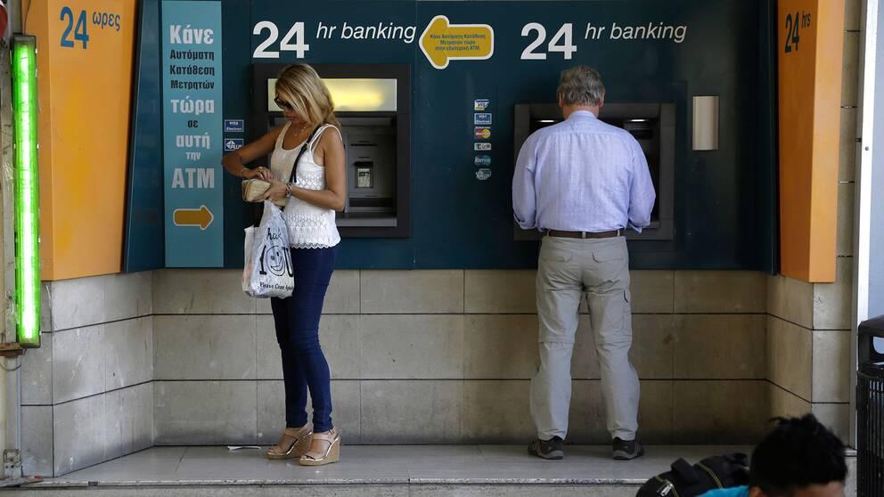 Två personer tar ut pengar